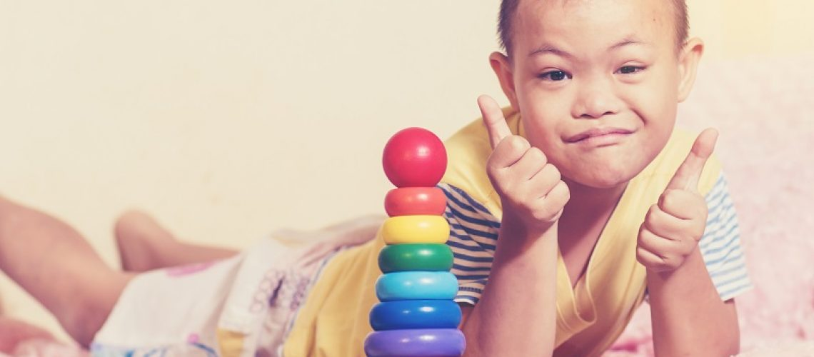 Little boy show two thumbs up when he complete question color wooden toy in the room