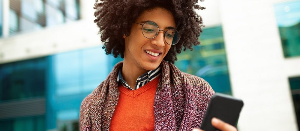 A handsome curly-haired guy of mixed race is dressed in a trendy youth-style scarf and sweater writes a message in a teleone against the background of office buildings. Youth culture.
