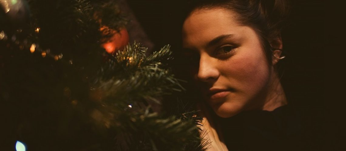 Pretty young girl dreaming of Christmas as she rests. A beautiful woman lies under a Christmas tree and enjoys loneliness.