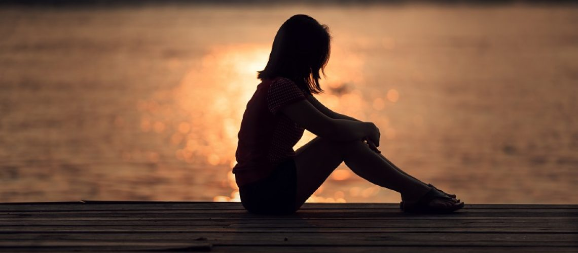 Sad woman silhouette worried at sunset