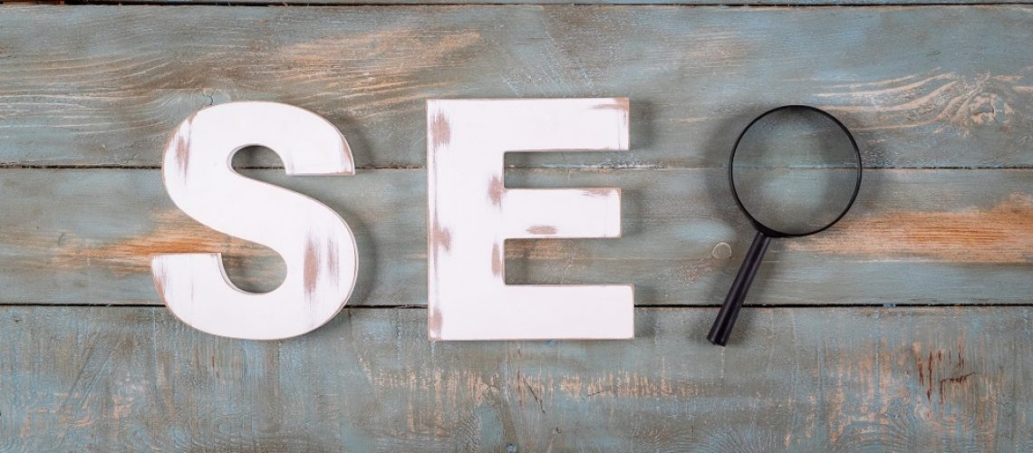 seo word formed with white letters and magnifying glass. Search engine optimization concept.